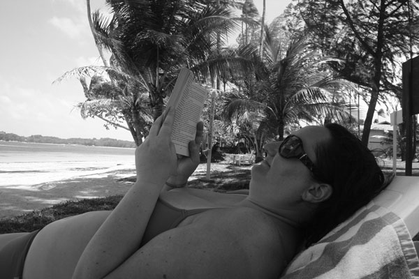 Jag läser på en strand på ön Bintan, Indonesien