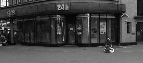 Tiggande kvinna utanför SEB i Riga