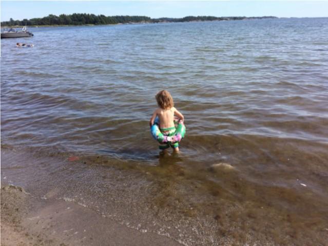Hugo badar i strandkanten på Järflotta