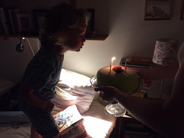 Yrvaken Hugo blåser ut fyra ljus i tårtan