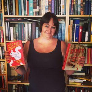 Jag stor framför bokhyllor och håller två böcker i handen. Nödrop från Lyckobubblan av Johanna Stenius och Skriet från kärnfamiljen av Rebecka Edgren Aldén och Tinni Ernsjöö Rappe.