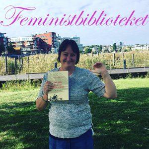 En bild på mig i Hammarby Sjöstad där jag bor. Jag håller en bok i ena handen, En sol bland döda klot av Anneli Furmark, och vinkar med den andra.